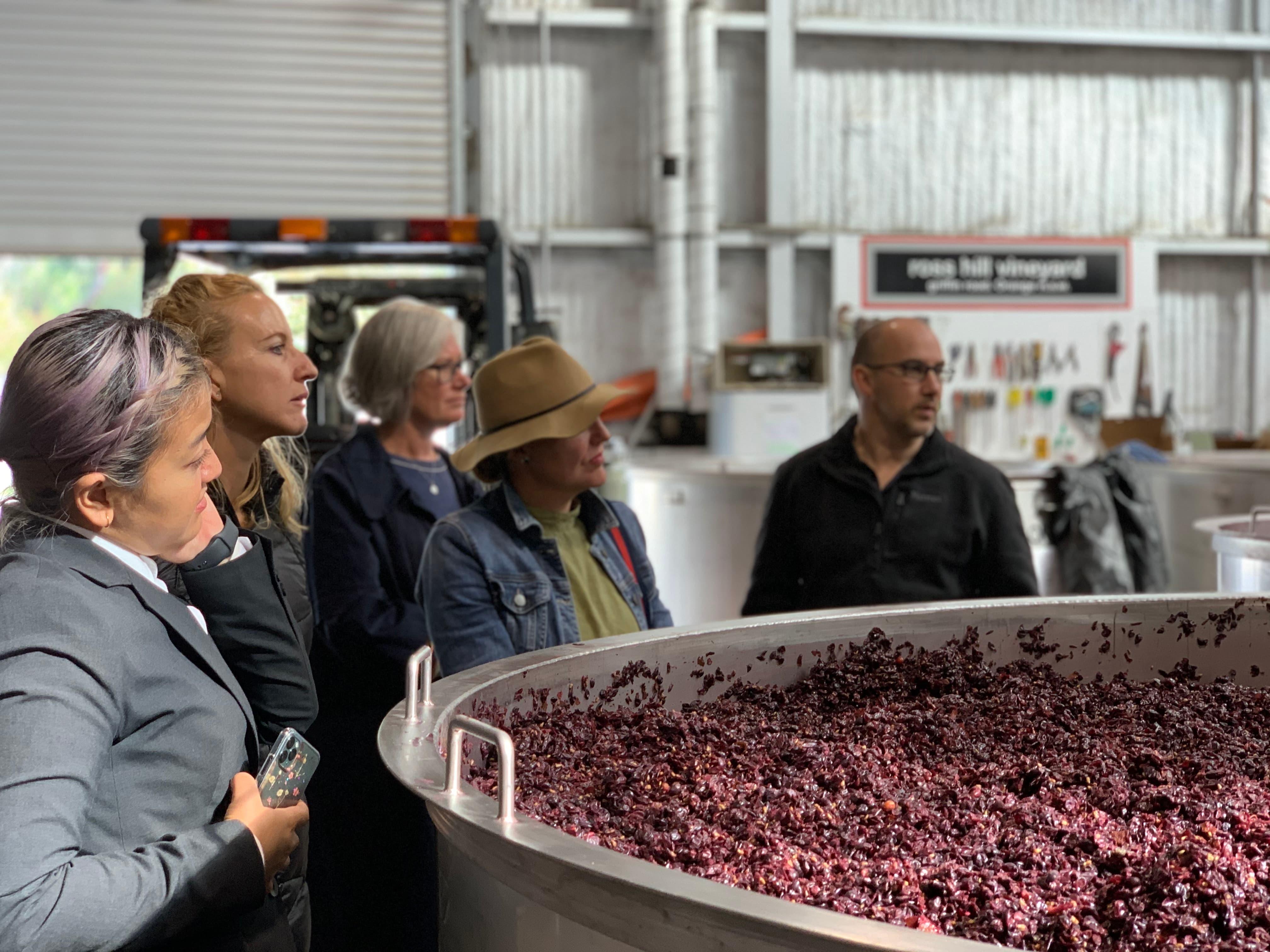 5 peopel standing near vat of wine