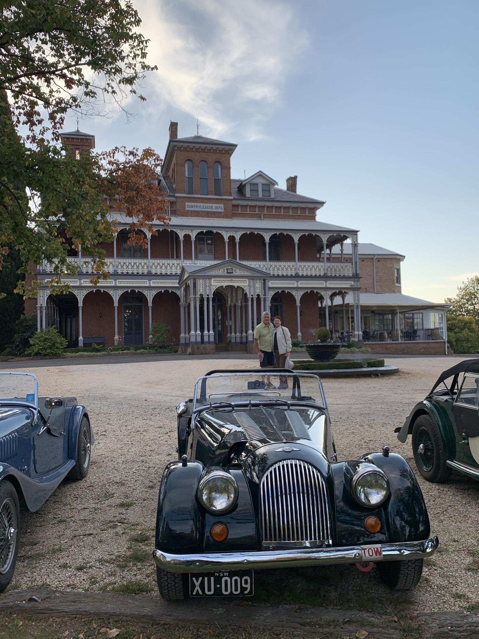 historic car in front of historic mansion