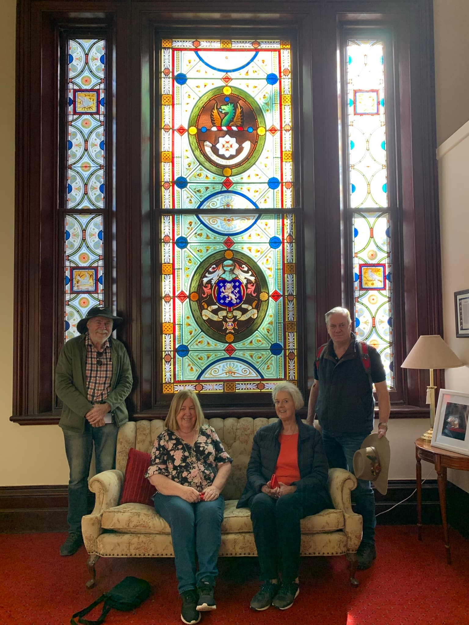 4 guests in front of stain glass windows