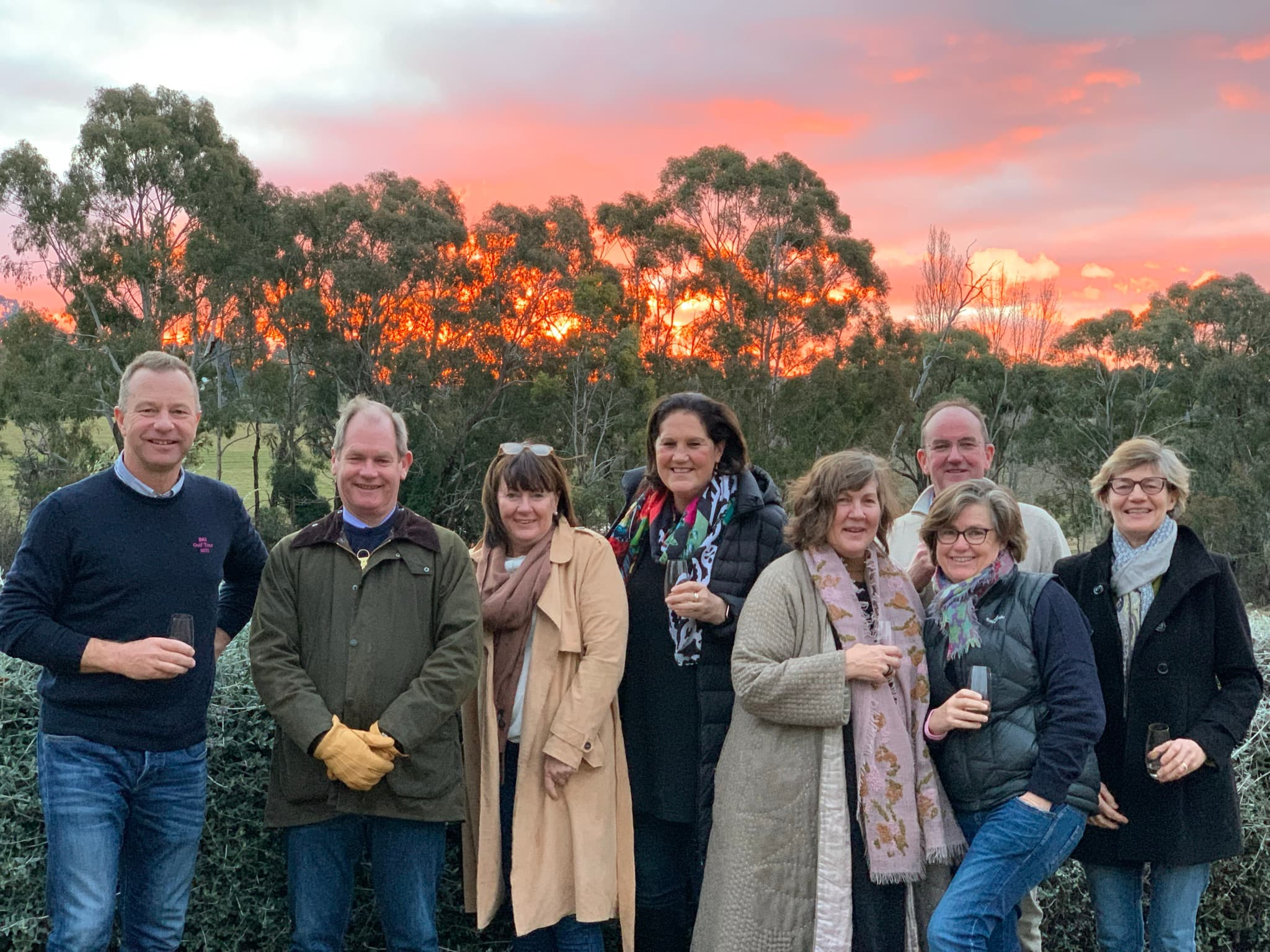 8 people standing in front of sunset