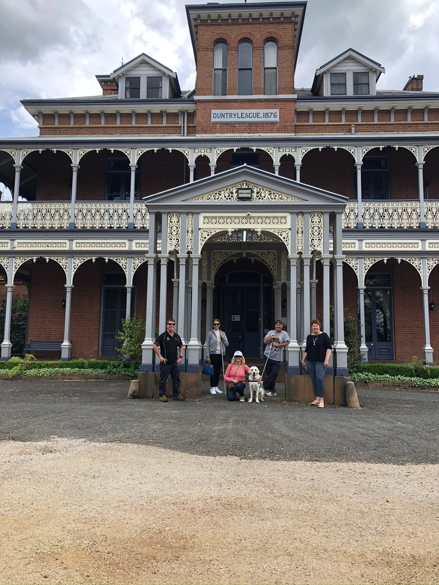 5 people standing in front of historic mansion with guide dog