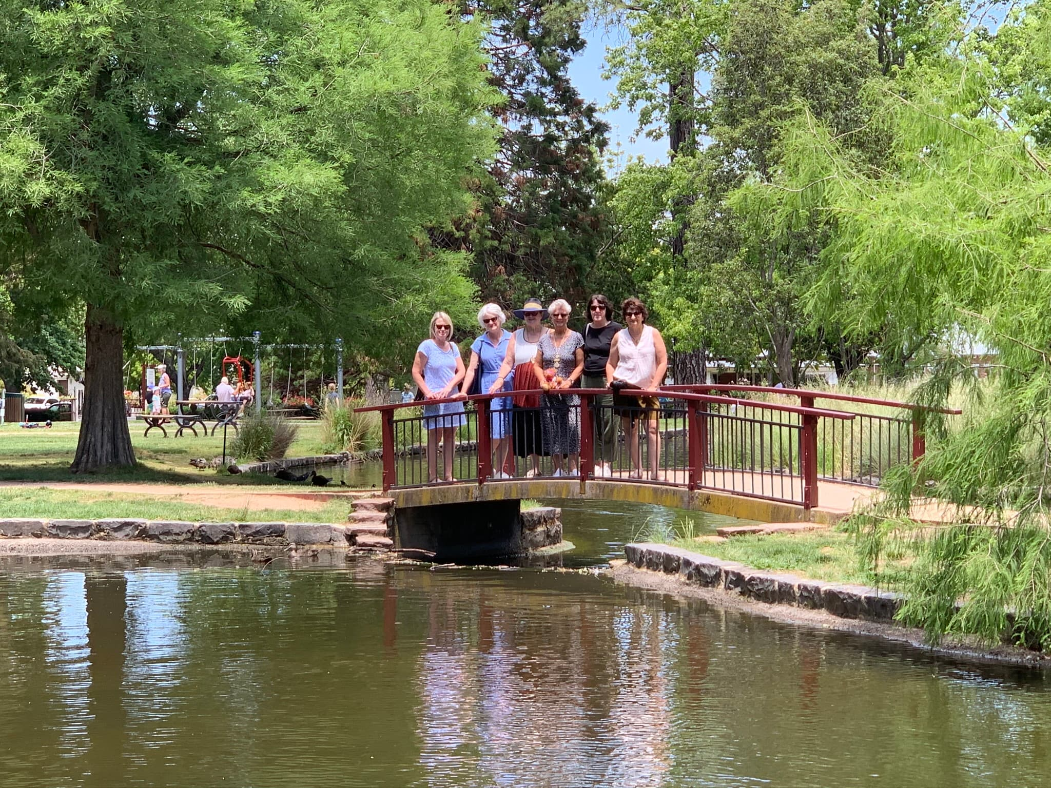 6 ladies standing on bridge over duck pond