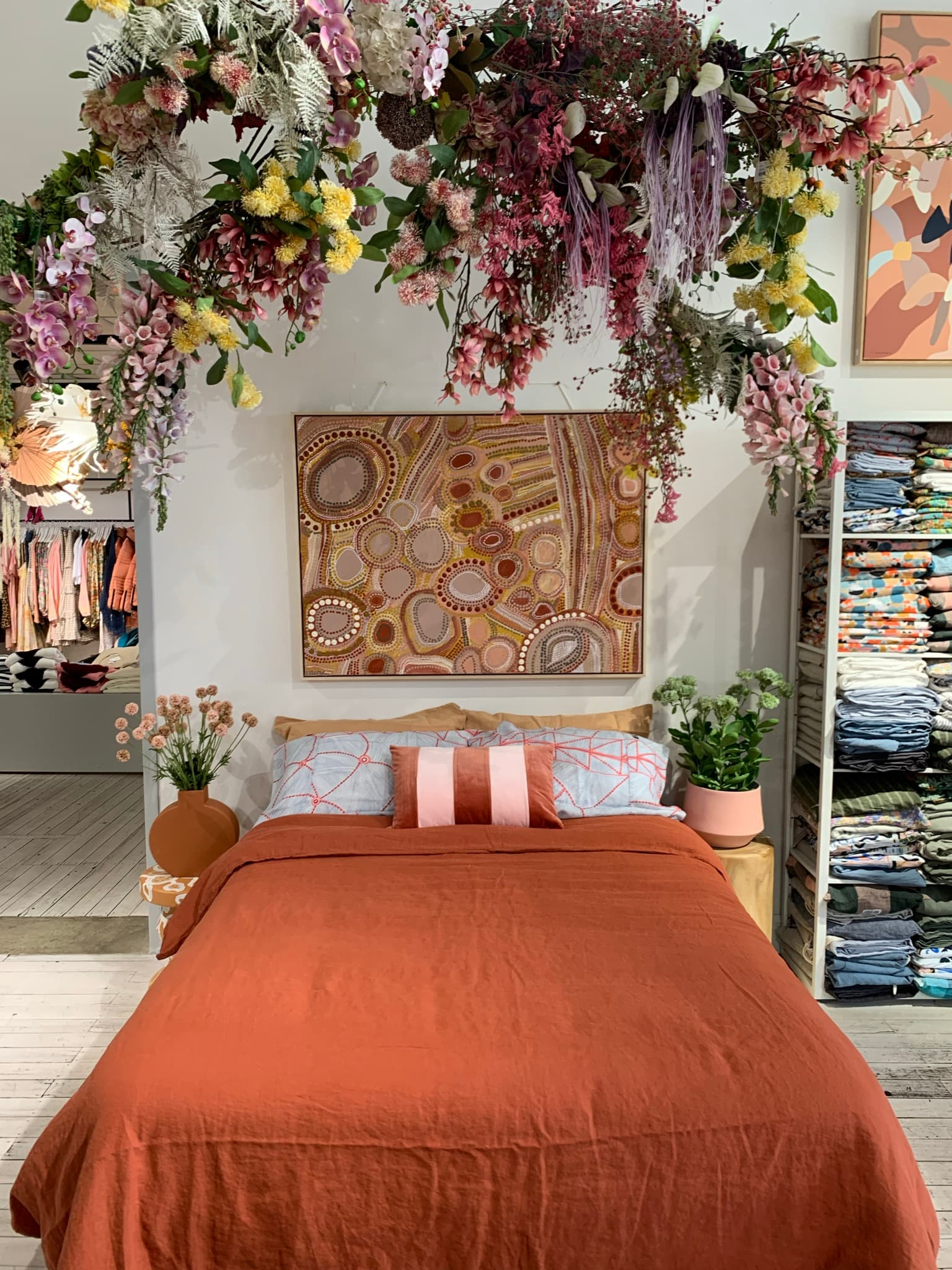 bed with orange bedspread and flowers above