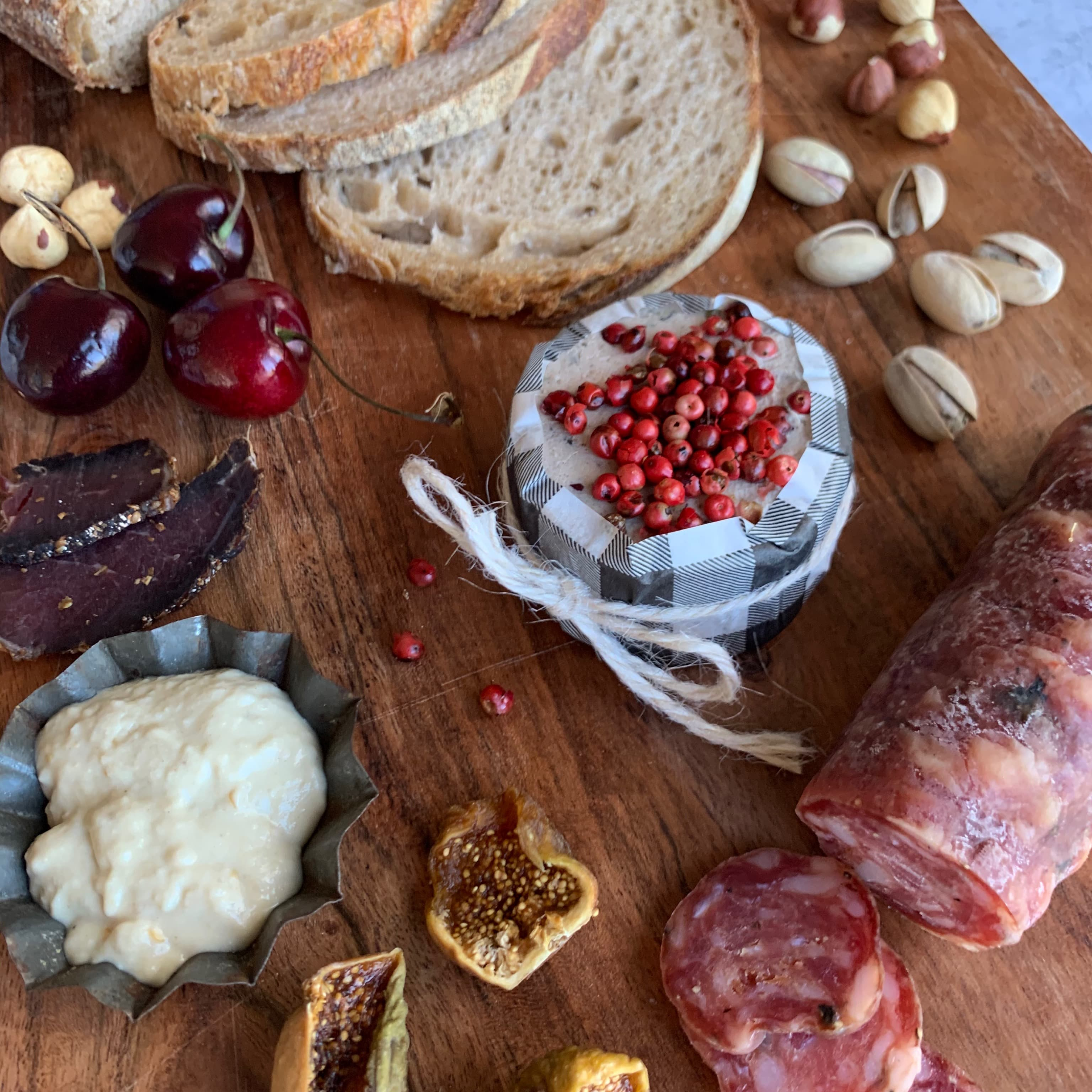meat, pate, dips and bread on wooden chopping board